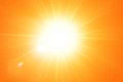 El sol brillante con la lente señala por medio de luces en el cielo anaranjado Imagen de archivo
