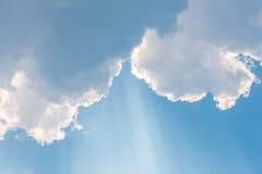 El sol brillante del fondo hermoso brilla a través de las nubes, rayo ligero fotografía de archivo
