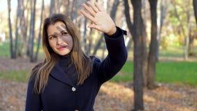 El sol brillante del otoño ciega a la mujer La muchacha mira el sol a través de los fingeres de su mano 4k 60fps se reducen almacen de video