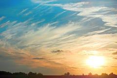 El sol contra el cielo azul nublado y un campo con los árboles en su Imágenes de archivo libres de regalías