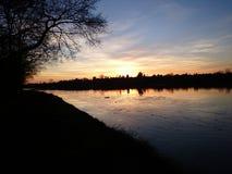 El sol de oro fija la etapa sobre el lago congelado inmóvil del hielo Imagen de archivo libre de regalías