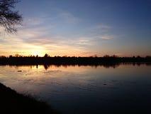 El sol de oro fija la etapa sobre el lago congelado inmóvil del hielo Fotos de archivo