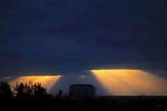 El sol de oro irradia estallar a través de las nubes azul marino Imagenes de archivo