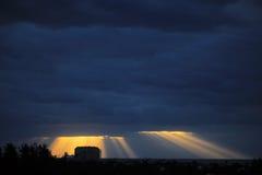 El sol de oro irradia estallar a través de las nubes azul marino Foto de archivo libre de regalías