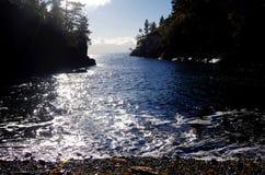 El sol del invierno chispea en las aguas azules de una pequeña bahía foto de archivo