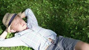 El sol del verano de la tarde se rompe a través de las ramas del ` de los árboles que brillan en el muchacho medio dormido almacen de metraje de vídeo