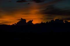 El sol detrás de las nubes antes de la puesta del sol Imágenes de archivo libres de regalías