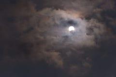 El sol durante un eclipse solar parcial con las nubes oscuras Imagenes de archivo