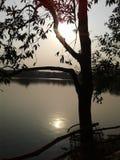 El sol, el cielo, árbol y agua Foto de archivo