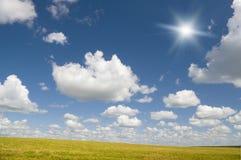 El sol en cielo azul arriba del prado floral. Imagenes de archivo