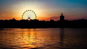 El sol en la puesta del sol a través de la noria Fotografía de archivo libre de regalías