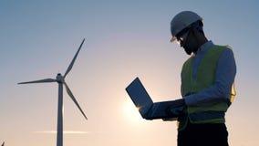 El sol está fijando mientras que un experto de la energética está observando un molino de viento Concepto limpio, respetuoso del  almacen de metraje de vídeo