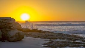 El sol fija detrás del espray de una onda de fractura en la playa de Noordhoek en la península del cabo en Suráfrica Imagenes de archivo