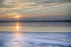 El sol fijado sobre el lago congelado Imagen de archivo libre de regalías