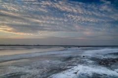 El sol fijado sobre el lago congelado Foto de archivo libre de regalías