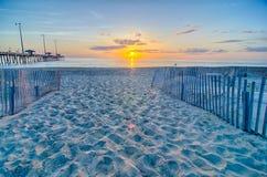 El sol naciente mira a escondidas a través de las nubes y se refleja en ondas cerca Imagen de archivo