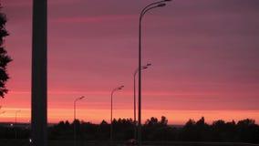 El sol naranja-rojo brillante sube sobre el camino, electro líneas de transmisión, edificios y árboles almacen de video