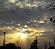 El sol oscuro de las nubes irradia el lanzamiento del iPhone del tiempo de la puesta del sol Foto de archivo