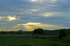 El sol poniente brilla a través de las nubes Foto de archivo libre de regalías