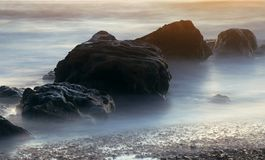 El sol poniente en el mar entre las piedras Imagen de archivo libre de regalías