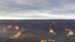 El sol poniente enciende para arriba las paredes lejanas de Grand Canyon Imagen de archivo libre de regalías