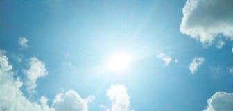 El sol que brilla brillantemente en el cielo azul nublado foto de archivo