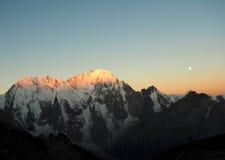 El sol se levanta sobre las nubes del mar y del oro Picos de montaña amanecer Luna Imagenes de archivo