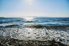 El sol va abajo al mar, las ondas en costa en remiendos soleados Fotografía de archivo