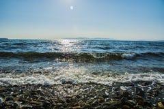 El sol va abajo al mar, las ondas en costa en remiendos soleados Fotos de archivo