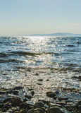 El sol va abajo al mar, las ondas en costa en remiendos soleados Foto de archivo libre de regalías