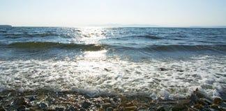 El sol va abajo al mar, las ondas en costa en remiendos soleados Fotografía de archivo libre de regalías