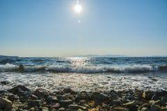El sol va abajo al mar, las ondas en costa en remiendos soleados Imagenes de archivo