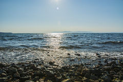 El sol va abajo al mar, las ondas en costa en remiendos soleados Imagen de archivo libre de regalías