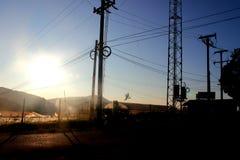 El sol y los posts de la electricidad Imagen de archivo