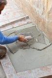 El solador trabaja con el suelo Foto de archivo