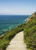 El solar de madera abajo a una costa azul de la playa salvaje del Océano Índico, isla de Robberg, Suráfrica, viaje Imagenes de archivo