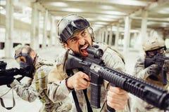 El soldado barbudo está gritando y está gritando Él tiene rifle largo en sus manos El individuo se está colocando delante de sus  imagen de archivo