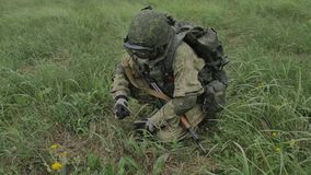 El soldado carga la cinta del máquina-arma de los cartuchos en un cajón almacen de video