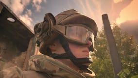 El soldado caucásico pensativo en camuflaje está pareciendo directo mientras que se coloca con el arma al aire libre, el sol está almacen de metraje de vídeo