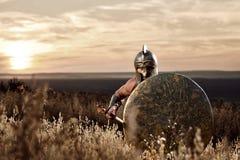 El soldado como espartano en la tenencia de bronce del casco redondeó el escudo Imagenes de archivo