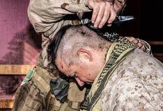 El soldado corta el pelo de los camaradas con el condensador de ajuste o las podadoras imagenes de archivo