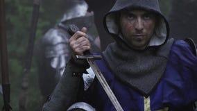 El soldado de edades medievales es que se incorpora y de limpieza de su espada, cierre almacen de metraje de vídeo