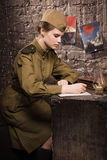 El soldado de sexo femenino soviético en el uniforme de la Segunda Guerra Mundial escribe una letra Fotos de archivo