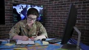 El soldado del retrato de la muchacha del personal militar en vidrios y el camuflaje uniforman, trabajando con el ordenador portá almacen de video