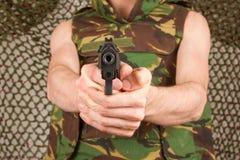 El soldado en chaleco del camuflaje está sosteniendo un arma Foto de archivo libre de regalías