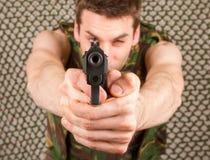 El soldado en chaleco del camuflaje está sosteniendo un arma Fotografía de archivo