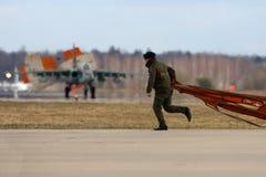 El soldado escoge el paracaídas para arriba caído del aeroplano de Sukhoi Su-25 de la fuerza aérea rusa durante ensayo del desfil Fotos de archivo libres de regalías
