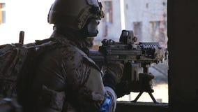 El soldado está teniendo como objetivo la blanco con la ametralladora almacen de metraje de vídeo