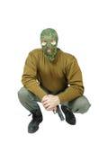 El soldado que se sienta con la pistola tiene un resto Imagenes de archivo