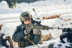 El soldado que sostiene un arma y la toma tienen como objetivo al enemigo Imagen de archivo libre de regalías